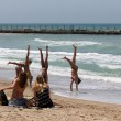 Girls doing acrobatics on the beach — Stock Photo