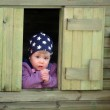 Beautiful little girl in the children's wooden house — Stock Photo #24785259