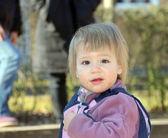 Beautiful little girl playing in the yard in sandbox — Stock Photo