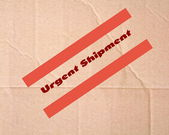 Urgent shipping sign on cardboard — Stock Photo