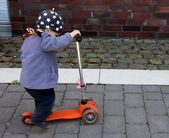 Little girl is trying to ride a large scooter — Stock Photo