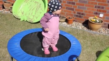 Little girl is trying to jump on the trampoline — Stock Video