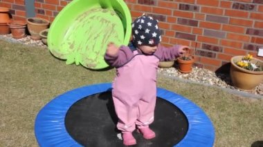Little girl is trying to jump on the trampoline — Vidéo