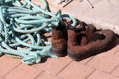 Brown work boots and blue rope — Stock Photo
