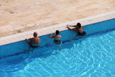 Group of tourists take water treatments at swimming pool by the Dead sea — Stock Photo