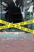 Police line do not cross sign tape on damaged by explosion building background — Stock fotografie