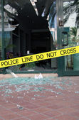 Police line do not cross sign tape on damaged by explosion building background — Stock Photo