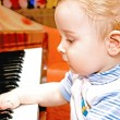 The small child plays a piano — Stock Photo