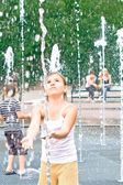 The girl in the fountain plays in the water — Stock Photo