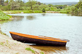 Wooden boat, stands on the Bank of the pond — Stock Photo