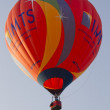 Orange IMTS Balloon sailing in sky - Stock Photo