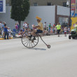 Man with Cheesehead Riding High Wheel Bicycle in parade — Stock Photo
