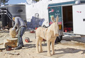 Man using Chainsaw to carve a donkey wood carving — Stock Photo