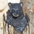 Stock Photo: Black Bear Cub peaking out of Stump wood carving