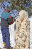Homem cinzelando detalhes de urso enorme do log com motosserra — Fotografia Stock