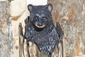 Black Bear Cub peaking out of Stump wood carving — Stock Photo