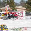 Stock Photo: Red and Black Polaris Snowmobile Racer Pointing to crowd