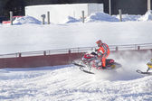 Red and Black Polaris Snowmobile Racing over jump — Stock Photo