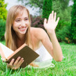 Stock Photo: Close-up portrait of young womwith book on grass