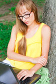 Young woman at the garden with laptop — Stock Photo
