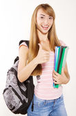 Smiling female student with books in hands and thumb up — Stock Photo
