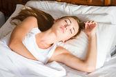 молодая женщина, спать на кровати — Стоковое фото