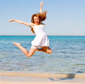 Happy young beautiful woman jumping on the beach — Stock Photo