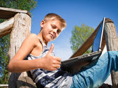 Boy with laptop on the nature — Foto Stock