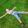 Happy boy lying on the grass outdoors — Stock fotografie