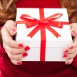 Royalty-Free Stock Photo: Christmas woman with gift and red manicure