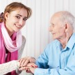 Senior man with her caregiver at home — Stock Photo #15333813