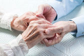 Old man's hands holding woman's hands — Stock Photo