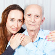 Senior man with her caregiver at home — Stok fotoğraf