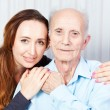 Senior man with her caregiver at home — Stockfoto