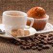 Cup of coffee, grains on burlap background — Stock Photo