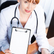 Female doctor showing blank clipboard — Stock Photo