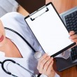Female doctor showing blank clipboard — Stock Photo #20727199