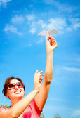 Woman starts paper plane in blue sky. — Stock Photo