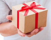 Male hand holding gift with ribbon. — Stock Photo