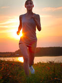 Portrait of young woman jogging in nature — Stock Photo