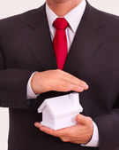Businessman holding house in the hands. — Stock Photo