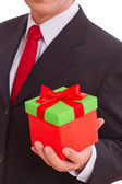 Businessman holding gift box with red bow — Stock Photo