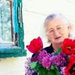 Portrait of an elderly woman with flowers — Stock Photo