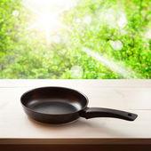 Lege koekenpan op houten achtergrond. — Stockfoto