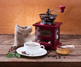 Cup of warm coffee and grinder. — Stock Photo