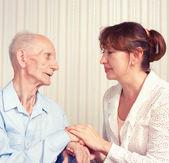 Senior hombre, mujer con su cuidador en casa. — Foto de Stock