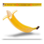 Large banana and measuring tape as image of man's penis — Stock Photo