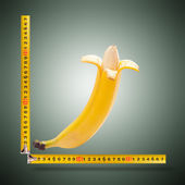 Large banana and measuring tape — Stock Photo