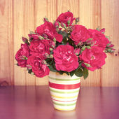Flowers in a vase on wooden table old — Stock Photo