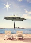 Two shizlong and umbrella on beach. — Stock Photo